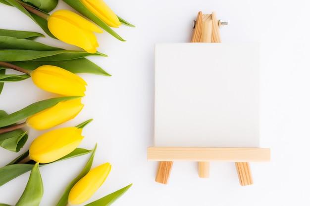 Lay piatto con fiori di tulipano giallo, cornice immagine vuota su sfondo bianco. concetto per biglietto di auguri per la pasqua, la festa della mamma, la giornata internazionale della donna, il giorno di san valentino