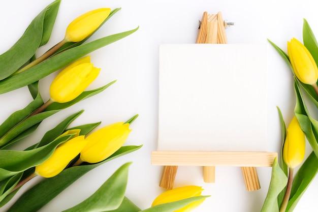 Lay piatto con fiori di tulipano giallo e cornice immagine vuota.