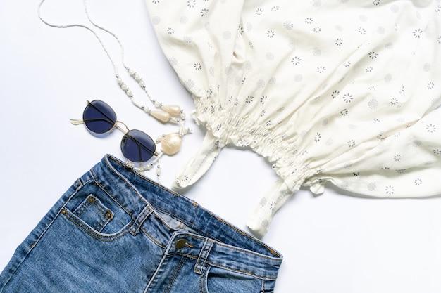 Piatto posare di vestiti e accessori donna con occhiali, borsetta.