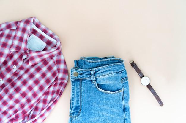 La disposizione piana dei vestiti e degli accessori della donna ha messo con i vetri. sfondo moda femminile alla moda.