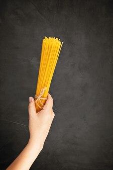 Piatto di laici donna mano che tiene gli spaghetti per cucinare la pasta italiana oltre il muro scuro. vista dall'alto del concetto di cucina italiana tradizionale