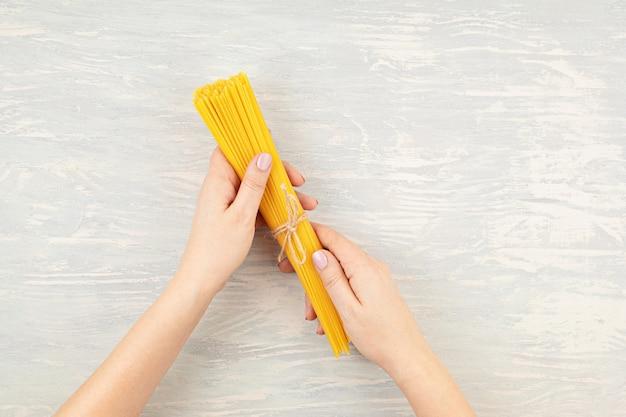 Piatto di laici donna mano che tiene gli spaghetti per cucinare la pasta italiana. vista dall'alto del concetto di cucina italiana tradizionale