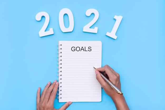 Mano di donna piatta laici che scrive i suoi obiettivi del nuovo anno in taccuino con il numero 2021 sulla parete blu. obiettivi del nuovo anno, concetto di pianificazione aziendale e finanziaria. copia spazio, vista dall'alto