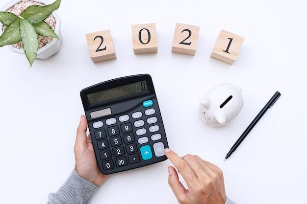 Piatto laici mani della donna utilizzando la calcolatrice sulla scrivania bianca obiettivi del nuovo anno concetto di pianificazione aziendale e finanziaria