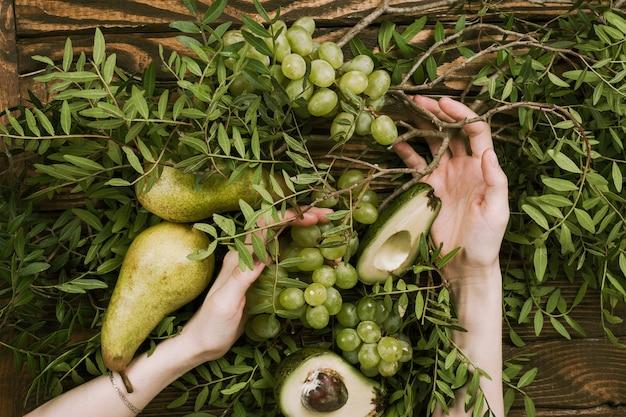 Disposizione piana delle mani della donna che tengono l'uva, le pere e gli avocado con i rami del pistacchio su di legno