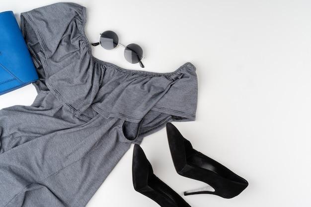 Disposizione piana dell'attrezzatura di estate della donna su fondo bianco