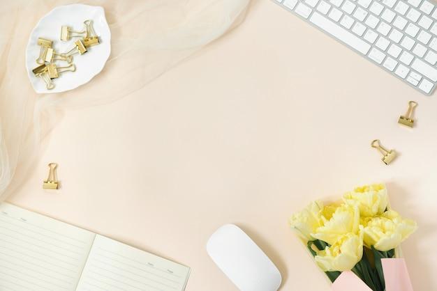 Scrivania da donna piatta. area di lavoro femminile con tastiera, bouquet di tulipani, accessori, diario, occhiali su uno sfondo di carta beige con spazio di copia. vista dall'alto sfondo femminile.