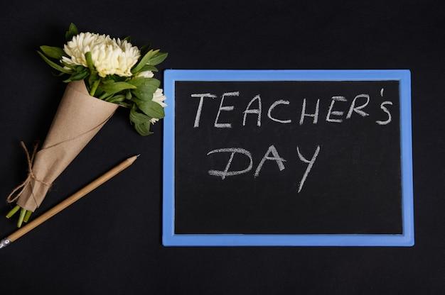Piatto disteso di matita di legno e bellissimo bouquet di fiori di astri in carta da regalo artigianale sdraiato accanto a una lavagna con scritta giornata dell'insegnante, isolato su sfondo nero con spazio di copia