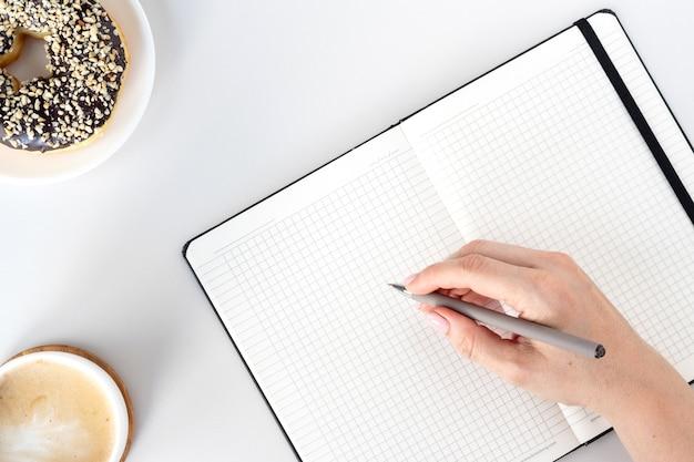 Disposizione piatta della scrivania dell'area di lavoro, taccuino aperto, penna, caffè, ciambella al cioccolato e mano di donna woman