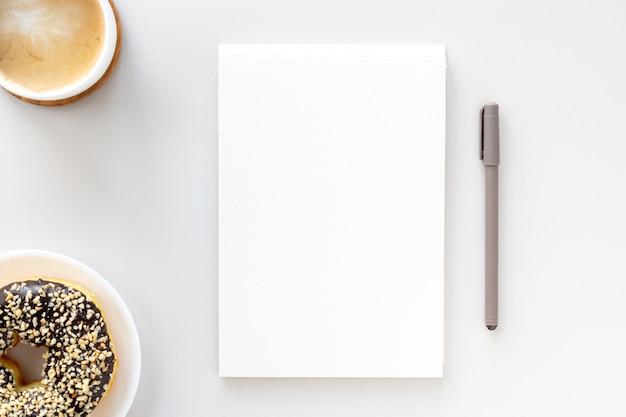 Disposizione piatta della scrivania dell'area di lavoro, taccuino aperto, penna, caffè e ciambella al cioccolato