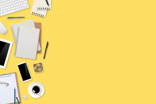 Tavolo da lavoro piatto con computer portatile, forniture per ufficio, tazza di caffè, tablet e telefono cellulare su sfondo giallo pastello