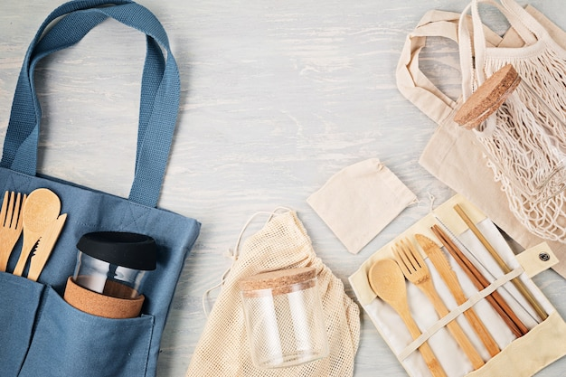 Kit per posa piatta zero waste. set di posate in bambù ecologiche, borsa in cotone a rete, bicchiere da caffè riutilizzabile, spazzole e bottiglia d'acqua. stile di vita sostenibile, etico, senza plastica. vista dall'alto