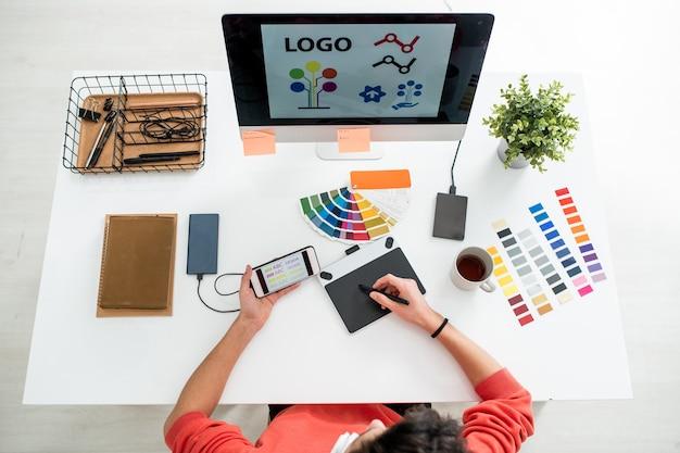 Layout piatto del giovane web designer con stilo e tavoletta grafica scegliendo il tipo di stampa per il logo sullo schermo del computer