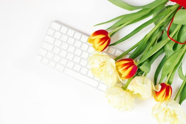 Fondo di san valentino piatto sdraiato con tastiera del computer e bouquet di tulipani. vista dall'alto di primavera.