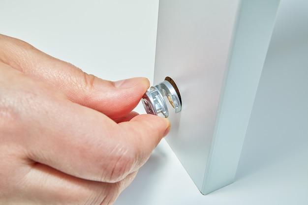 Servizio di assemblaggio di mobili in confezione piatta a casa, assemblatore di mobili inserisce il dado.