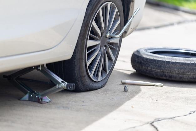 Gomma a terra i dadi dei bulloni con una chiave inglese e ruota di scorta che sostituisce la ruota, cambio pneumatico sull'auto, concetti di riparazione e manutenzione