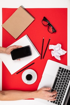 Vista piana della scrivania da ufficio con una disposizione creativa di cancelleria e quaderni per il desktop.
