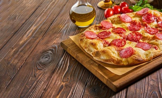 Pizza ai peperoni fatta in casa con focaccia su tavola di legno