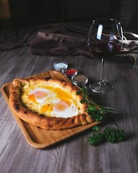 Focaccia con igname e formaggio nel ristorante. piatto con vino ed erbe aromatiche. Foto Premium