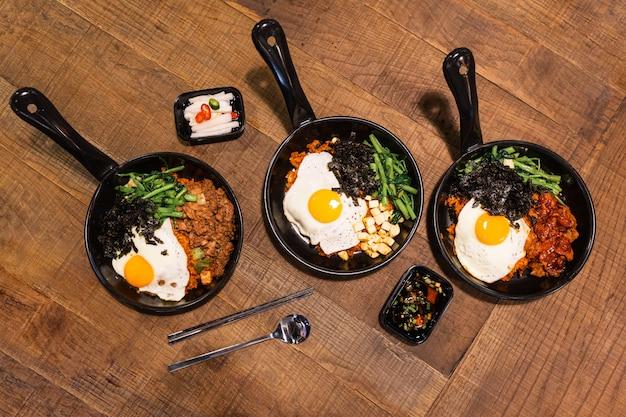 Flatlay di bibimbap (riso coreano mescolato con carne di maiale kimchi, tofu, alghe e verdure fritte condite con sesamo) servito sulla padella calda.
