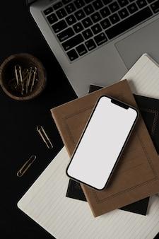 Flatlay di smart phone mobile con schermo vuoto, laptop, notebook, clip in ciotola di legno su sfondo nero.