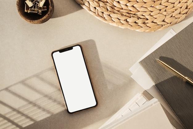 Flatlay di smartphone con schermo vuoto, notebook, clip in una ciotola di legno, supporto di paglia su fondo di cemento beige. area di lavoro della scrivania dell'ufficio domestico.