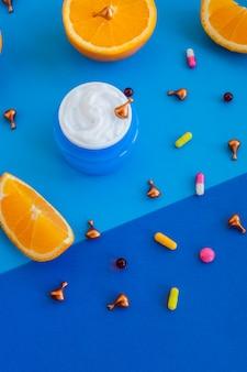 Composizione flatlay con olio, pillole, vitamine, capsule, crema per il viso, agrumi e arance sulla parete blu. concetto di bellezza naturale prodotto cosmetico vitaminico, cura della pelle. aroma terapia di bellezza