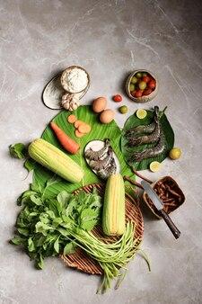 Preparazione degli ingredienti da cucina flatlay, preparazione della zuppa di spinaci (sayur bayam) e tempura di gamberi. composizione di ingredienti freschi crudi con copia spazio per testo/pubblicità