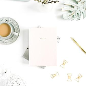 Flatlay del tavolo della scrivania dell'home office. area di lavoro con taccuino rosa pastello pallido e decorazioni su sfondo bianco. disposizione piatta, vista dall'alto