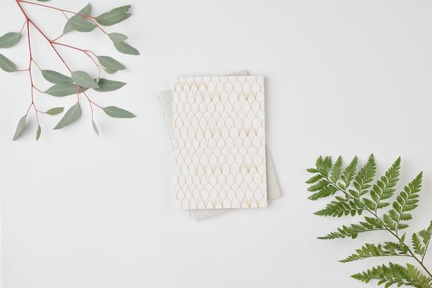 Flatlay di notebook su laptop piegato contro uno spazio bianco circondato da rami con foglie verdi