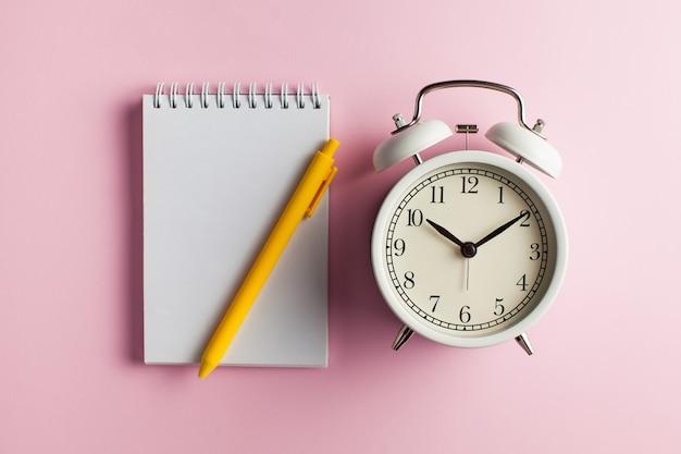 Taccuino, penna e sveglia flatlay su una superficie rosa