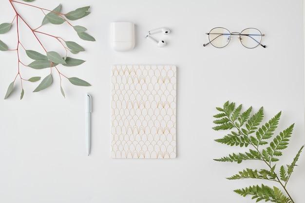 Flatlay di notebook con penna, occhiali da vista e auricolari su uno spazio bianco circondato da piante verdi