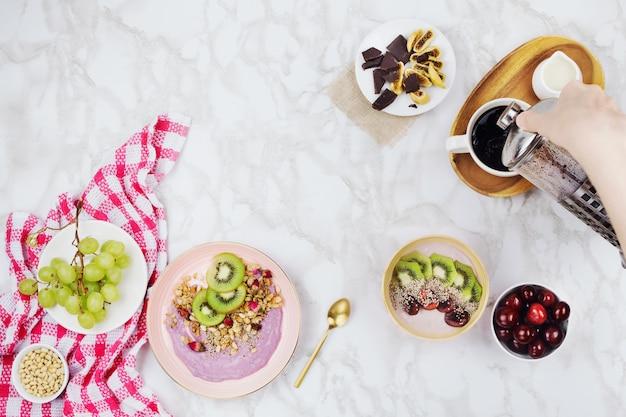Flatlay di colazione vegana con scodelle di yogurt a base vegetale condite con fette di kiwi, muesli, semi di chia, bottiglia di frullato e caffè con latte di soia su sfondo di marmo