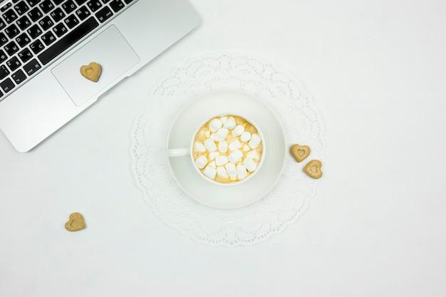 Un flatlay di una tazza bianca di cappuccino con marshmallow, zucchero di canna sotto forma di cuori e un laptop su sfondo bianco