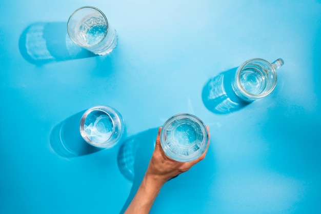 Flatlay con bicchieri di acqua frizzante pulita e la mano della donna che tiene una tazza. concetto sano, sfondo blu