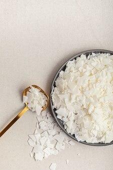Flatlay con fiocchi di cera di soia bianca biologicacandele fatte a mano, fai da te, idea per hobby