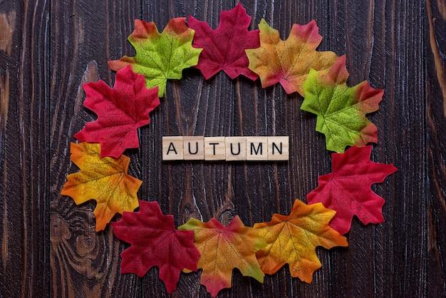 Flatley autunno fogliame d'acero iscrizione autunnale in lettere di legno sul tavolo tema dell'umore autunnale