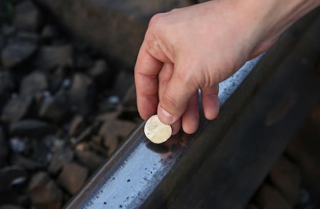 Appiattire le monete sui binari ferroviari all'aperto.