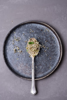 Germogli di lino e di erba medica in cucchiaio su sfondo grigio, microgreens germinati, concetto di nutrizione sana.