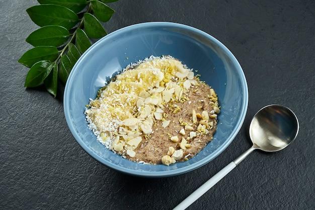 Porridge di lino con banane, noci, cioccolato e cocco in una ciotola blu su una superficie nera