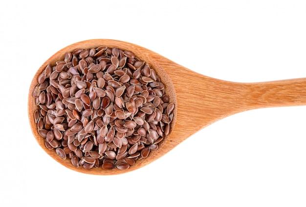 Mucchio dei semi di lino in cucchiaio di legno isolato su fondo bianco
