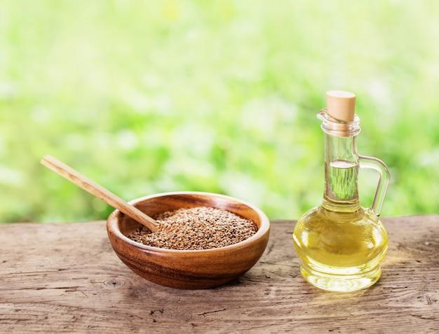 Semi di lino e olio di lino in una brocca di vetro su un tavolo di legno