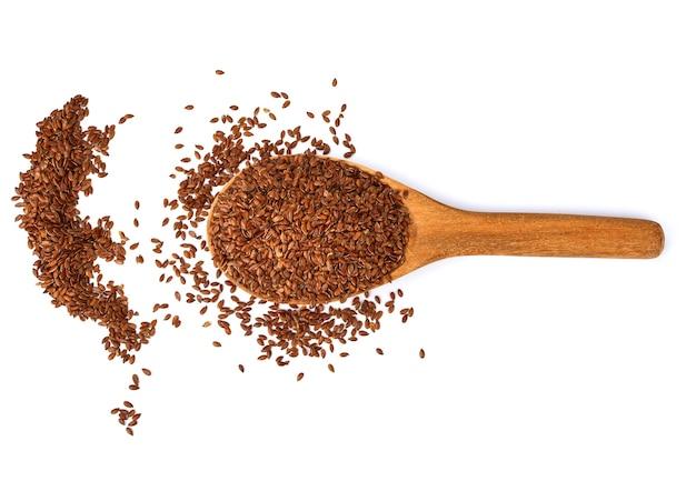 Semi di lino in un cucchiaio di legno isolato su superficie bianca.