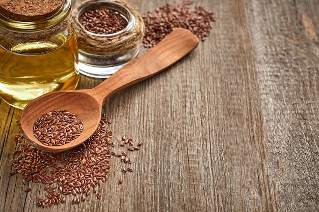 Semi di lino e un cucchiaio di legno con la bottiglia di olio su una tavola di legno