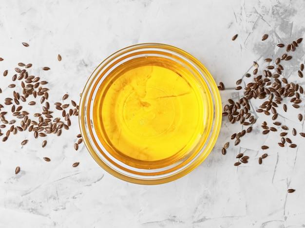 Olio di semi di lino in una ciotola di vetro e semi di lino dorati su una superficie grigia