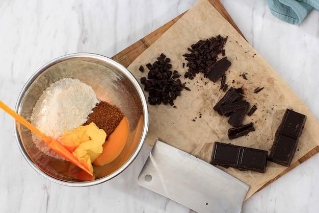 Flay lay ingredienti makinh biscotti con scaglie di cioccolato, farina, uova, burro sulla ciotola, cioccolato tritato sul tagliere