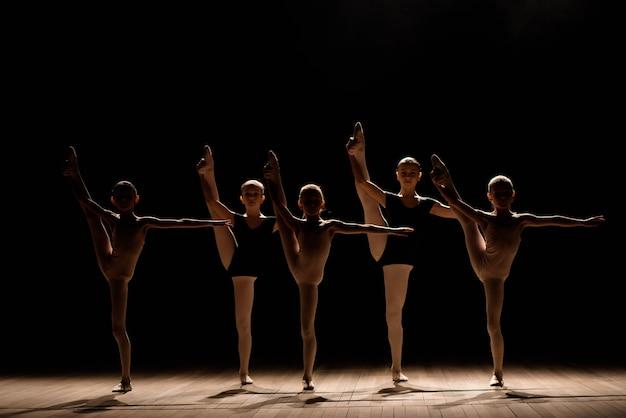Ballerine flessibili si allungano su una scena scura e illuminata.