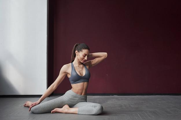 Flessibile e grazioso. la ragazza con un buon tipo di corpo fitness ha esercizi nella stanza spaziosa