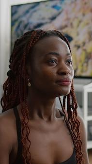 Donna esile flessibile con pelle nera che pratica esercizio respiratorio
