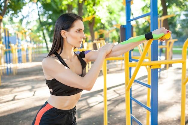 Donna castana muscolare sbalorditiva flessibile che porta vestito nero sportivo, allungando il braccio. giovane atleta femminile fiducioso che pratica ginnastica, riscaldamento, kinesiotaping colorato sul corpo.